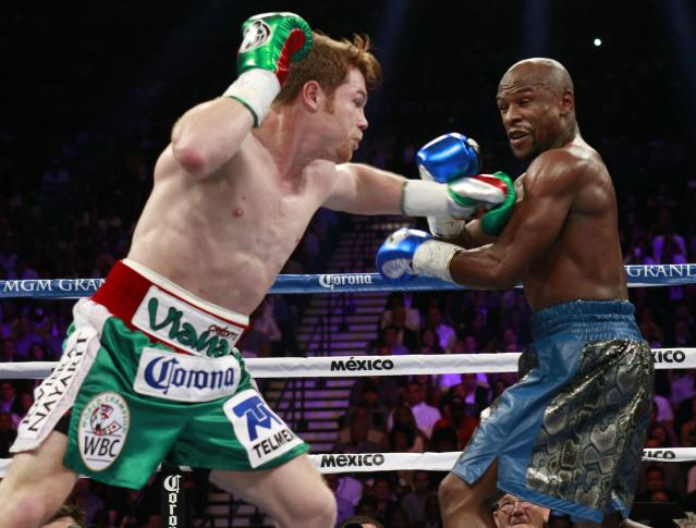 WBC/WBA 154-pound champion Canelo Alvarez (L) fights against Floyd Mayweather Jr. of the U.S. at the MGM Grand Garden Arena in Las Vegas, Nevada, September 14, 2013. REUTERS/Steve Marcus (UNITED STATES - Tags: SPORT BOXING)