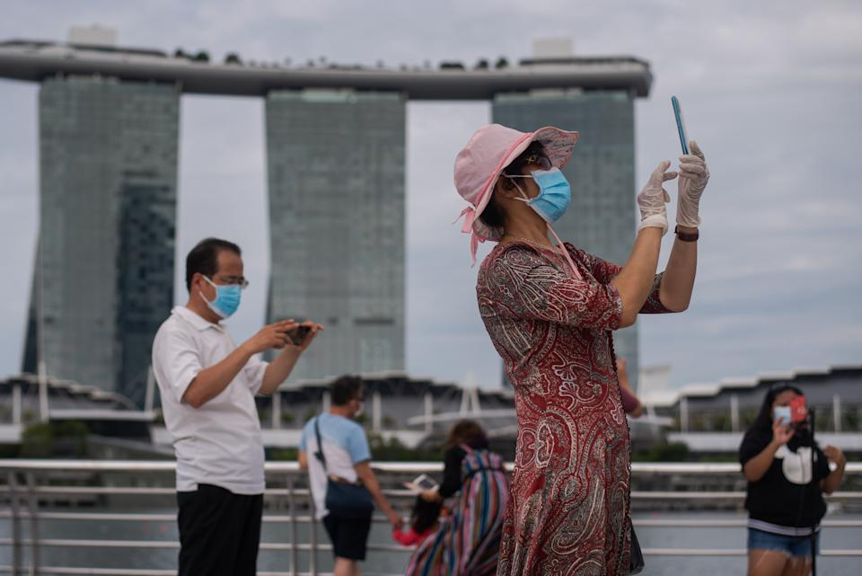 A woman wearing 2 masks and gloves takes pictures at Singapore's Marina Bay on Sunday, 1st August 2021 in SIngapore. Community cases have risen steadily as the largest Covid-19 cluster that began in Singapore's main fishing port weeks ago has since reported more than 1000 cases linked to it yesterday. (Photo by Joseph Nair/NurPhoto via Getty Images)