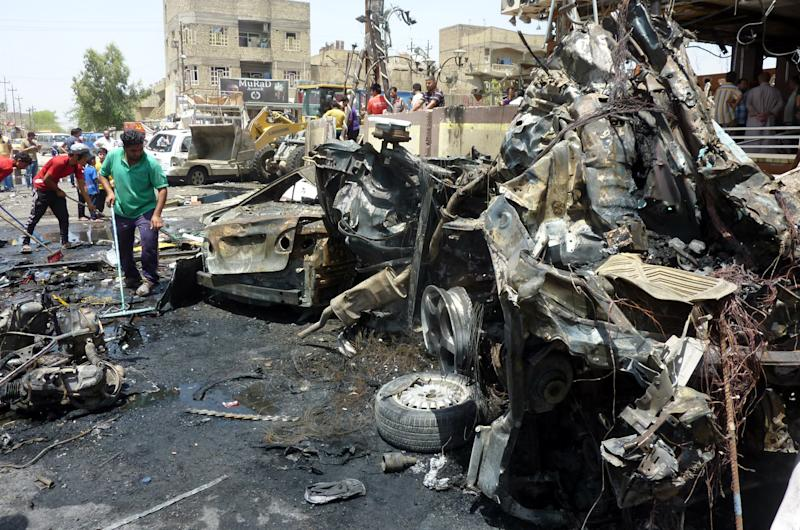 Iraqi men clear the debris at the scene of a car bomb in the mainly Shiite Sadr City district in Baghdad on August 1, 2014