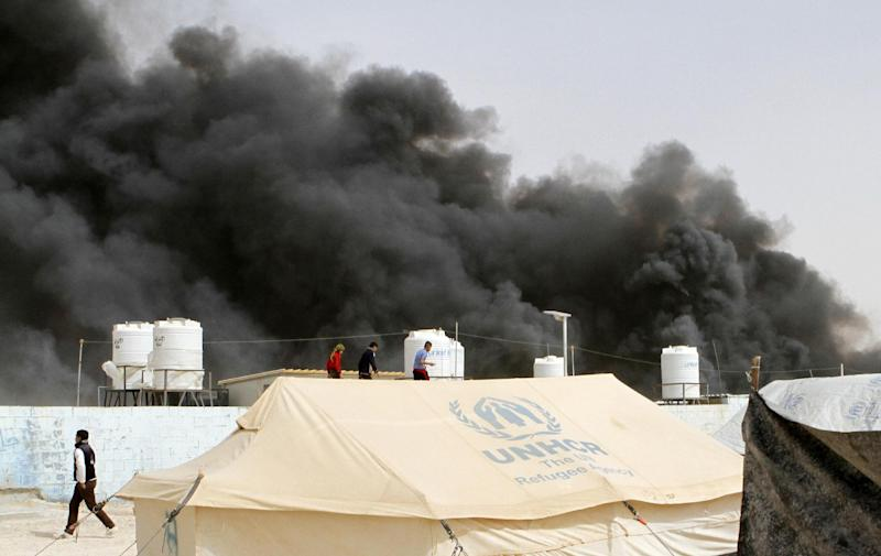Syrian refugees watch as a fire sends black smoke rising over the Zaatari refugee camp in northeast Jordan, Friday, March 8, 2013. The U.N. refugee agency says a fire broke out in Jordan's Zaatari camp for Syrian refugees but reported no major injuries or deaths in the blaze that burned at least 20 or more tents, including some hosting small shops. (AP Photo: Raad Adayleh)