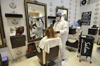 NOIDA, INDIA - JUNE 9: A hairdresser wearing PPE seen at work inside a salon in Smart Bharat Mall after in reopened to the public yesterday following the relaxations in lockdown restrictions at Sector 25A on June 9, 2020 in Noida, India. (Photo by Sunil Ghosh/Hindustan Times via Getty Images)