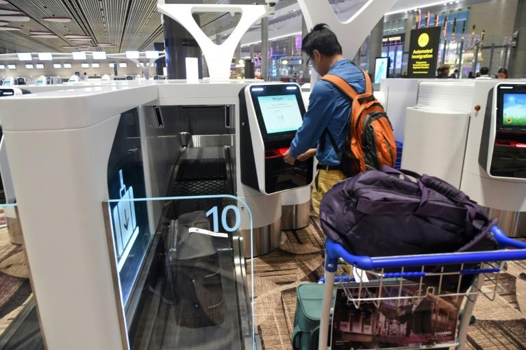 A passenger checks-in his luggage using an automated booth at the newly opened Changi International Airport's Terminal 4 in Singapore
