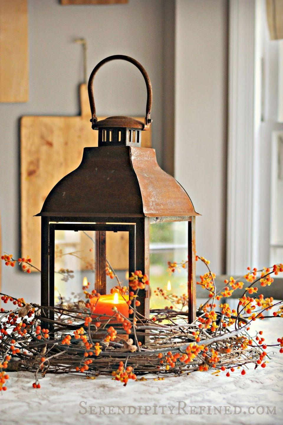 """<p>Light up your table in style with a vintage lantern surrounded by fall branches. </p><p><strong>Get the tutorial at <a href=""""http://www.serendipityrefined.com/2014/10/rusty-lantern-and-bittersweet-simple.html"""" rel=""""nofollow noopener"""" target=""""_blank"""" data-ylk=""""slk:Serendipity Refined"""" class=""""link rapid-noclick-resp"""">Serendipity Refined</a>.</strong></p><p><strong><a class=""""link rapid-noclick-resp"""" href=""""https://go.redirectingat.com?id=74968X1596630&url=https%3A%2F%2Fwww.wayfair.com%2Fdecor-pillows%2Fpdp%2Fthree-posts-wooden-lantern-thps8743.html&sref=https%3A%2F%2Fwww.countryliving.com%2Fentertaining%2Fg2130%2Fthanksgiving-centerpieces%2F"""" rel=""""nofollow noopener"""" target=""""_blank"""" data-ylk=""""slk:SHOP LANTERNS"""">SHOP LANTERNS</a></strong></p>"""