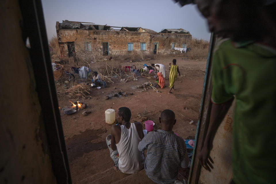 Tigrayan refugees who fled Ethiopia's conflict, prepare to cook their dinners in front of their temporary shelters, at Umm Rakouba refugee camp in Qadarif, eastern Sudan, Saturday, Dec. 12, 2020. (AP Photo/Nariman El-Mofty)