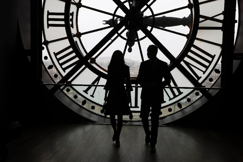 Britain's Prince William and his wife Britain's Kate look across the River Seine at a view of Paris through the clock face at the Musee d'Orsay on March 18, 2017 (AFP Photo/FRANCOIS GUILLOT)