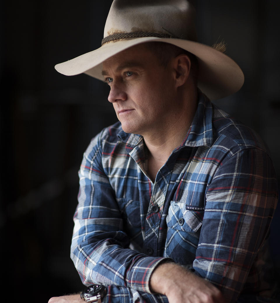 Grant Denyer wearing a cowboy hat and a blue plaid shirt in a promo photo for SBS' Who Do You Think You Are?