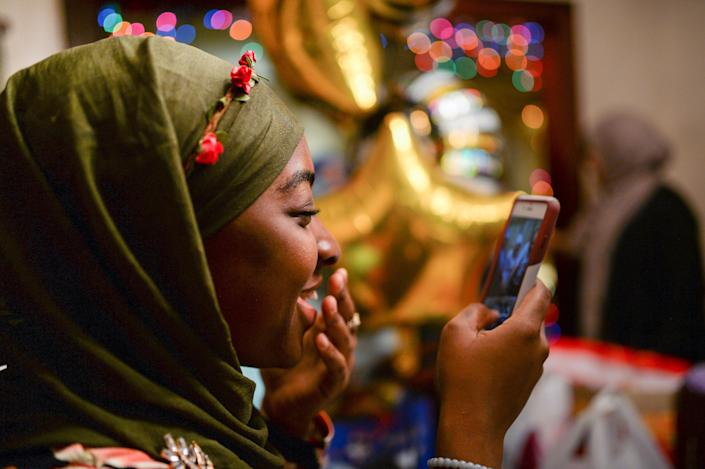 Halima Mahuoud, a Togolese Ghanaian American Muslim, smiles as she photographs her Egyptian American Muslim friend cutting cake at her graduation celebration and Iftar feast during Ramadan in Bayonne, New Jersey, U.S. June 2, 2017. Picture taken June 2, 2017. REUTERS/Amr Alfiky
