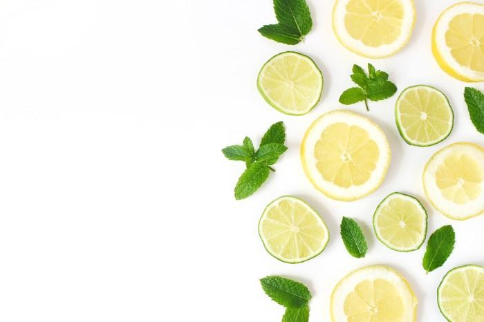 Sliced lemons and limes artfully arranged with mint leaves on a white table.