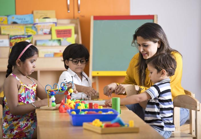 Teachers with children playing and learning at preschool