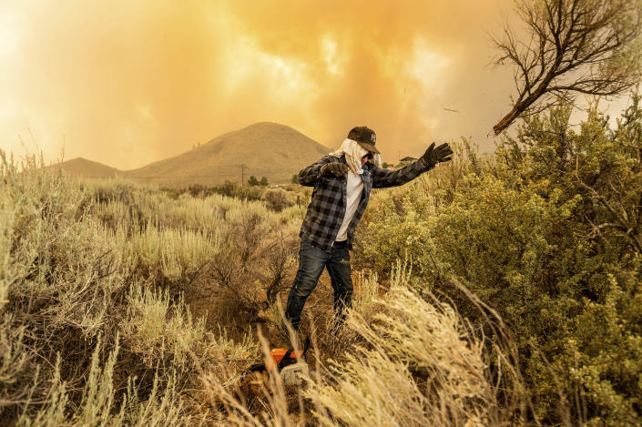 David Garfield clears a fire break around his home as the Sugar Fire, part of the Beckwourth Complex Fire, burns towards Doyle, Calif., on Saturday, July 10, 2021. (AP Photo/Noah Berger)