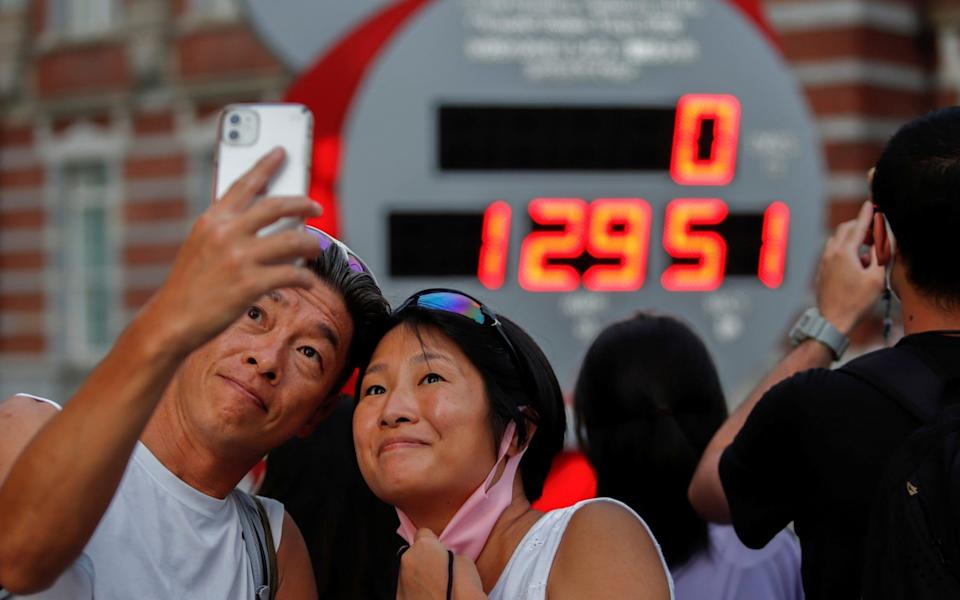 People take photos in front of the Tokyo Olympics countdown clock in front of Tokyo station - ANDRONIKI CHRISTODOULOU/REUTERS