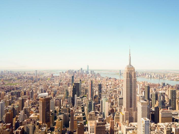 Buildings in Manhattan as seen from the tall One Vanderbilt building against a blue sky.