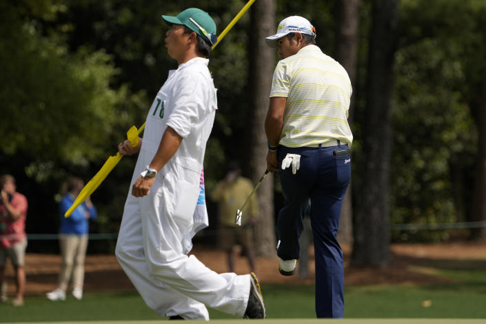 Hideki Matsuyama, of Japan, and his caddie Shota Hayafuji react after his missed par putt on the first green during the final round of the Masters golf tournament on Sunday, April 11, 2021, in Augusta, Ga. (AP Photo/David J. Phillip)