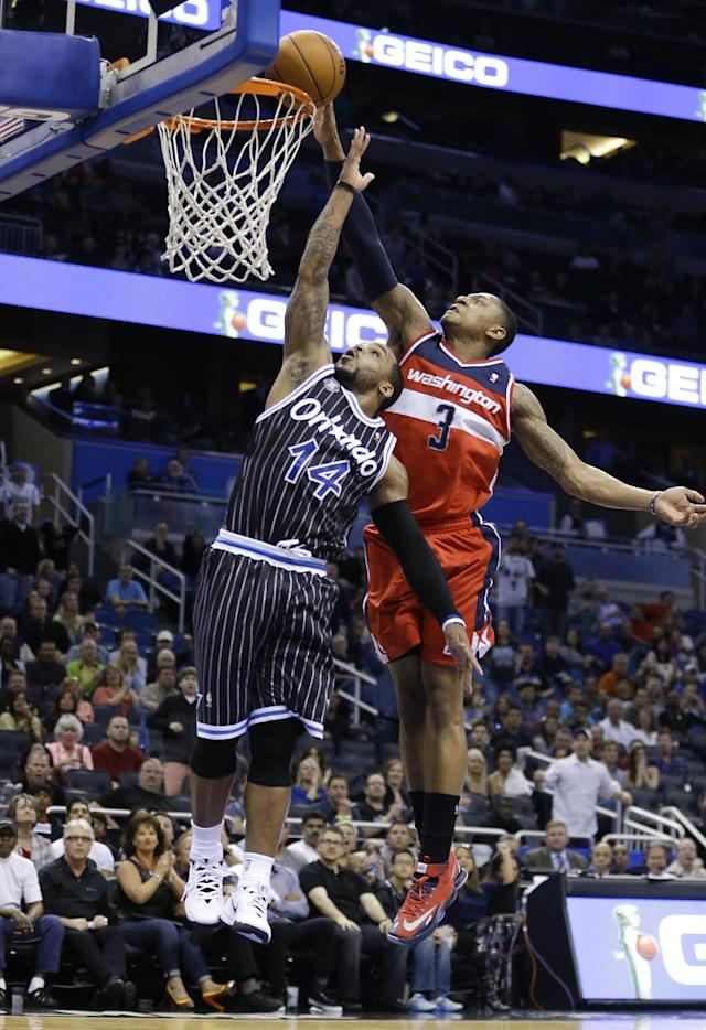 Washington Wizards' Bradley Beal (3) blocks a shot by Orlando Magic's Jameer Nelson (14) during the second half of an NBA basketball game in Orlando, Fla., Friday, March 14, 2014. Washington won in overtime, 105-101. (AP Photo/John Raoux)