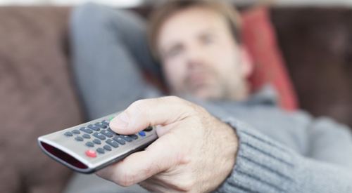 Man lying on couch with remote