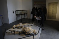 A woman takes pictures of casts of two victims of the 49 AD Eruption of Mount Vesuvius displayed at the museum Antiquarium, in Pompeii, southern Italy, Monday, Jan. 25, 2021. Decades after suffering bombing and earthquake damage, Pompeii's museum is back in business, showing off exquisite finds from excavations of the ancient Roman city. Officials of the archaeological park of the ruins of the city destroyed in 79 A.D. by the eruption of Mount Vesuvius inaugurated the museum on Monday. (AP Photo/Gregorio Borgia)