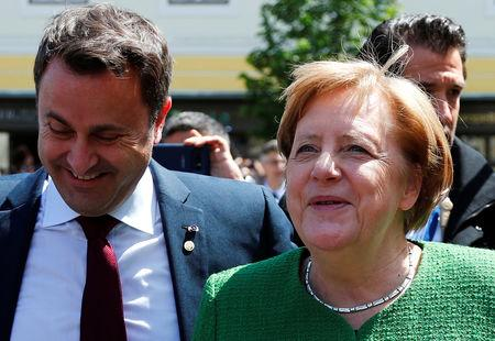 Luxembourg's Prime Minister Xavier Bettel and German Chancellor Angela Merkel react after the family photo opportunity during the informal meeting of European Union leaders in Sibiu, Romania, May 9, 2019. REUTERS/Francois Lenoir