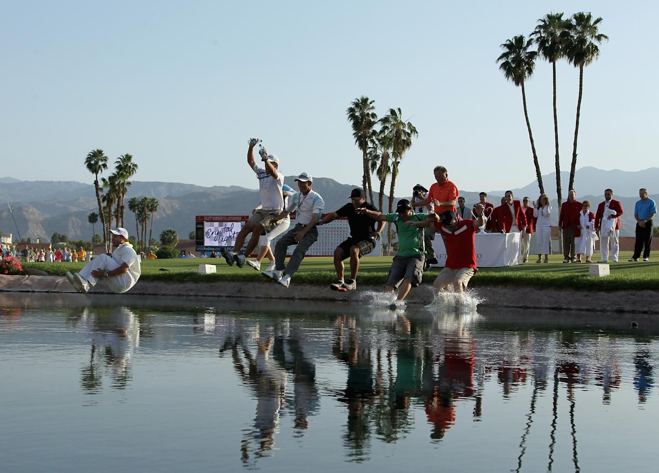 RANCHO MIRAGE, CA - APRIL 07:  Inbee Park of South Korea celebrates by jumping into Poppie's Pond along with caddie Brad Beecher, coach Chong Paek, fiance Gi Hyub Nam, Song Kang, O.H. Kwan, and Kyu Bum Huh after winning the Kraft Nabisco Championship at Mission Hills Country Club on April 7, 2013 in Rancho Mirage, California.  (Photo by Jeff Gross/Getty Images)