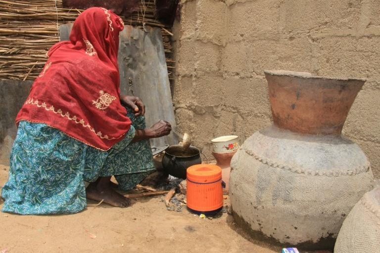 A woman cooks at the Yawuri camp on the outskirts of Maiduguri -- home to nearly 2,000 people displaced by the Boko Haram insurgency (AFP/Audu Marte)
