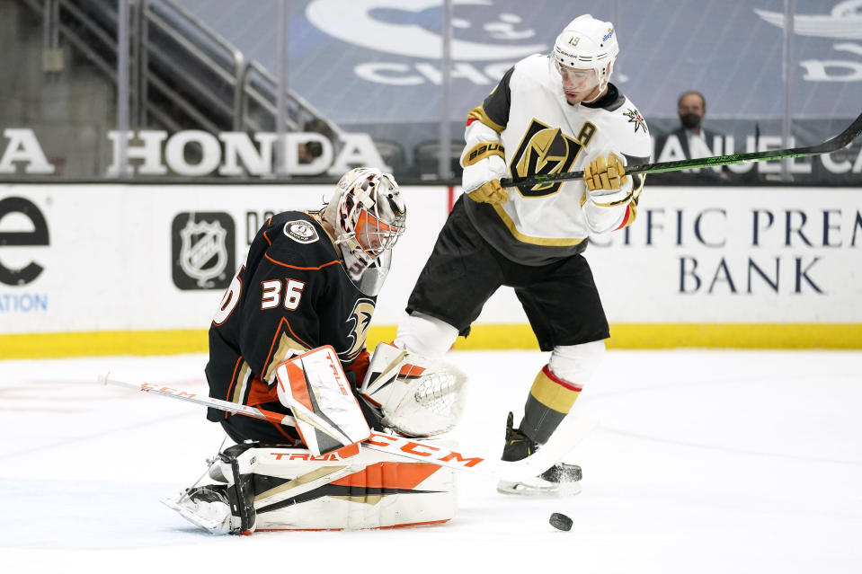 Anaheim Ducks goaltender John Gibson, left, deflects a shot as Vegas Golden Knights right wing Reilly Smith stands in front of him during the first period of an NHL hockey game Saturday, Feb. 27, 2021, in Anaheim, Calif. (AP Photo/Mark J. Terrill)