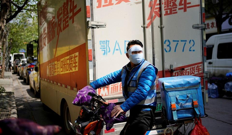 A delivery worker wearing a face mask is seen at a blocked residential area after the lockdown was lifted in Wuhan, Hubei province, April 13, 2020. Photo: Reuters