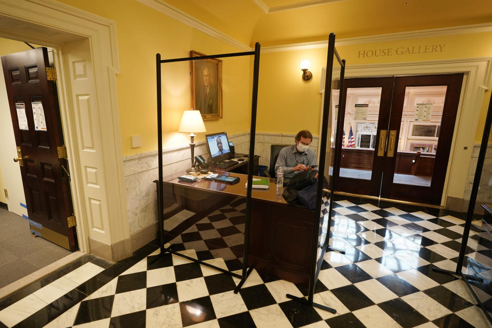 House telecommunications coordinator, Aubrey Stewart, monitors a Virginia House of Delegates Zoom Legislative meeting from the Gallery at the Capitol in Richmond, Va., Wednesday, Feb. 10, 2021. (AP Photo/Steve Helber)
