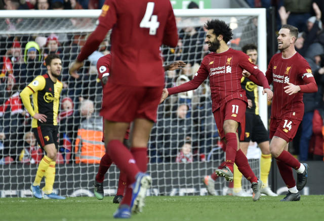 Liverpool's Mohamed Salah, 2nd right, celebrates with teammates after scoring his sides first goal during the English Premier League soccer match between Liverpool and Watford at Anfield stadium in Liverpool, England, Saturday, Dec. 14, 2019. (AP Photo/Rui Vieira)
