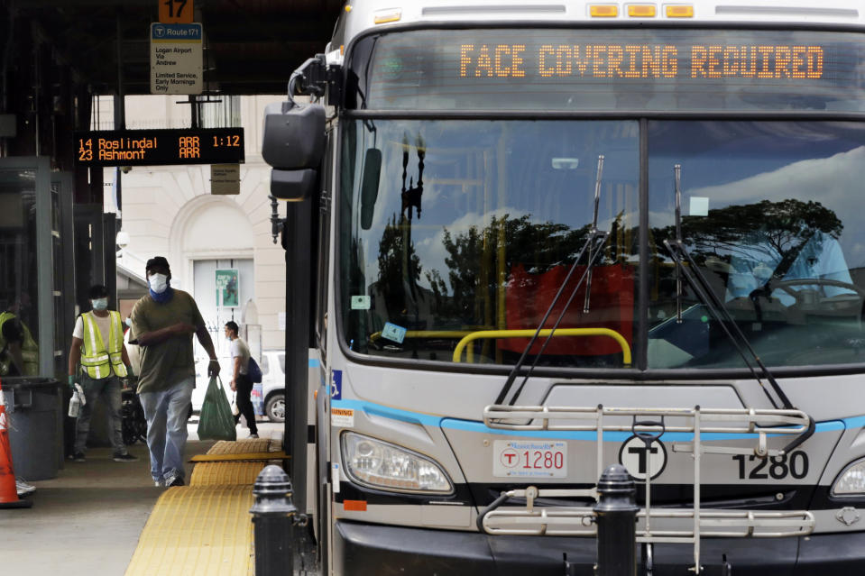 FILE- In this June 24, 2020, file photo, a man, wearing a protective face mask, rushes to catch his bus at Dudley Station in Nubian Square in Boston. Face coverings are required on all buses, subways, trains and trolleys in Boston due to the COVID-19 virus outbreak. The CDC is strongly recommending that passengers on planes, trains and buses wear masks, but it's still stopping short of requiring face coverings to prevent spreading COVID-19. The CDC says masks should be worn by all passengers and workers on planes, ferries, trains, subways, buses, taxis and ride-sharing vehicles. (AP Photo/Charles Krupa, File)
