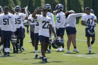 Seattle Seahawks rookie cornerback Tre Brown (22) carries helmets as he waves to fans after NFL football practice Wednesday, July 28, 2021, in Renton, Wash. (AP Photo/Ted S. Warren)