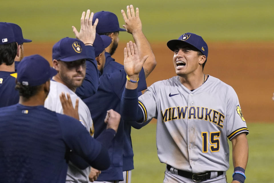 Milwaukee Brewers' Tyrone Taylor (15) high- fives his teammates after the Brewers defeated the Miami Marlins 6-2 in a baseball game, Saturday, May 8, 2021, in Miami. (AP Photo/Lynne Sladky)