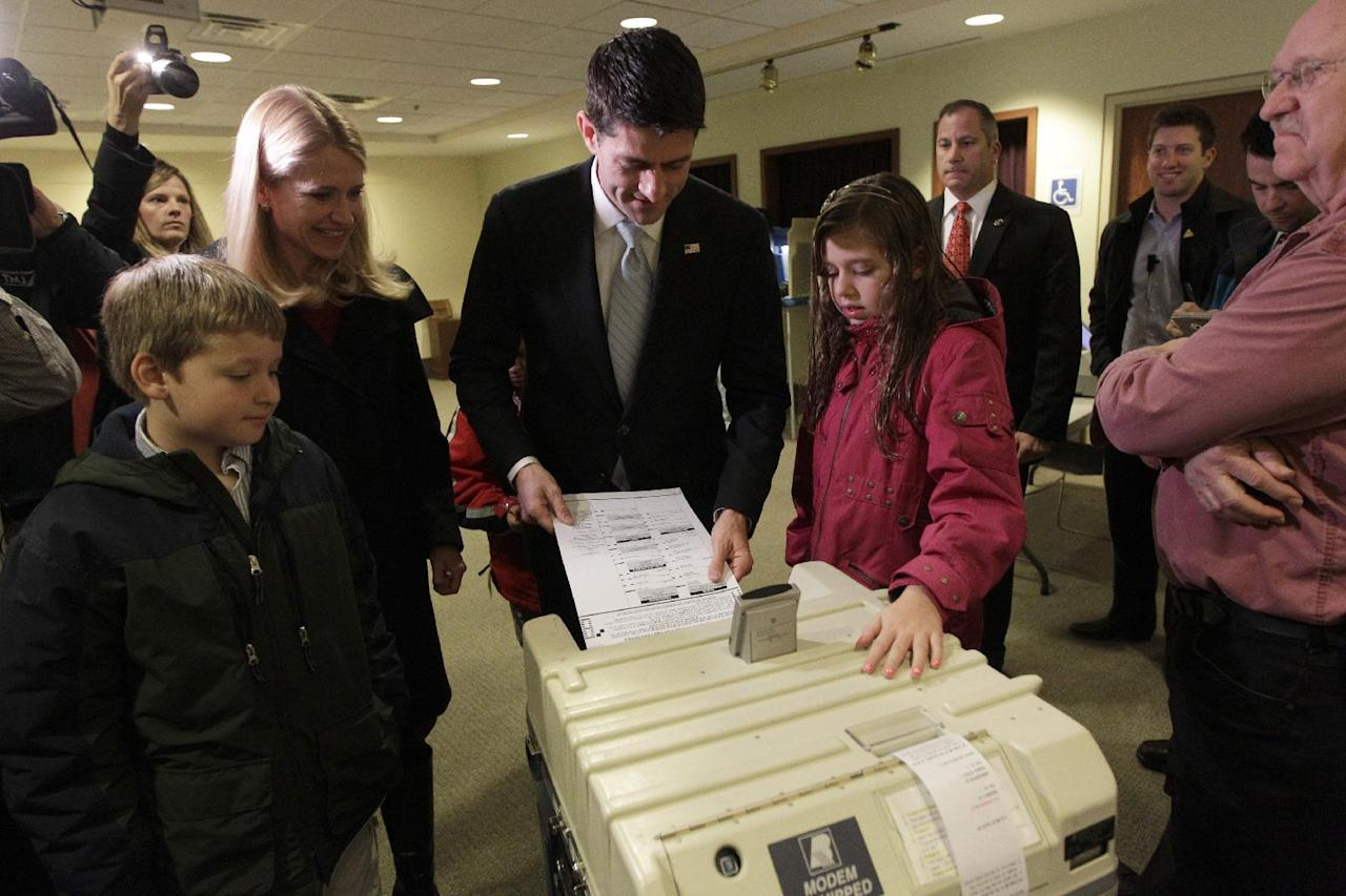 Republican vice presidential candidate, Rep. Paul Ryan, R-Wis., casts his ballot as his wife Janna, son Charlie, left and daughter Liza watch, Tuesday, Nov. 6, 2012 at the Hedberg Public Library in Janesville, Wis. (AP Photo/Mary Altaffer)
