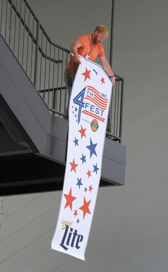 <p>Cody Thomas of the Owensboro Convention Center hangs a 10-foot, 4th Fest Celebration banner from the upper stairs railing on the backside of the OCC on Monday, July 3, 2017, during preparations for the 4th Fest Celebration along the riverfront in Owensboro, Ky. The 4th Annual 4th Fest Celebration starts at 4:00 p.m. and runs until 10:30 p.m. on Independence Day. (Photo: Alan Warren/The Messenger-Inquirer via AP) </p>