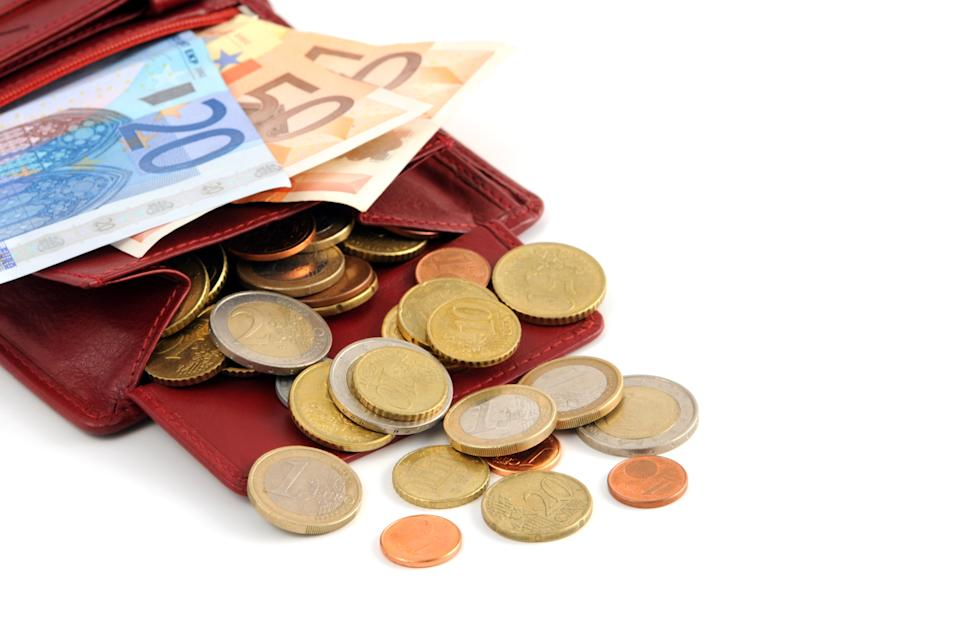 Euro coin and 2 x 50 Euro paper currency and 1 x 20 Euro paper currency falling out of walletmoney stocking.Business and money to sock away background of wealth.