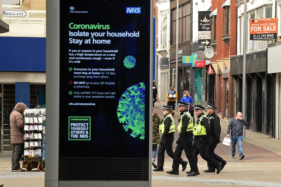 A group of police officers patrol Briggate in central Leeds on the morning of March 21, 2020, a day after the British government said it would help cover the wages of people hit by the coronavirus outbreak as it tightened restrictions to curb the spread of the disease. (Photo by Oli SCARFF / AFP) (Photo by OLI SCARFF/AFP via Getty Images)
