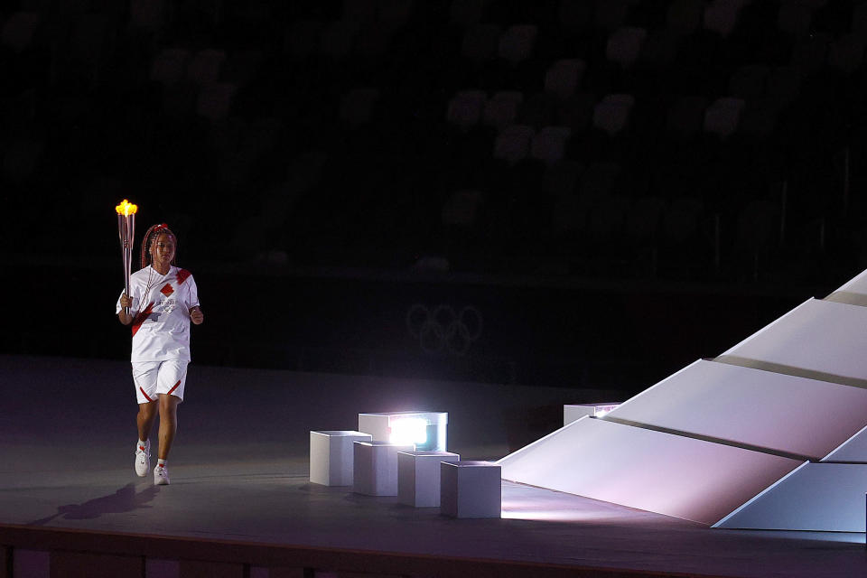 <p>TOKYO, JAPAN - JULY 23: Naomi Osaka of Team Japan carries the Olympic torch towards the Olympic cauldron during the Opening Ceremony of the Tokyo 2020 Olympic Games at Olympic Stadium on July 23, 2021 in Tokyo, Japan. (Photo by Maddie Meyer/Getty Images)</p>