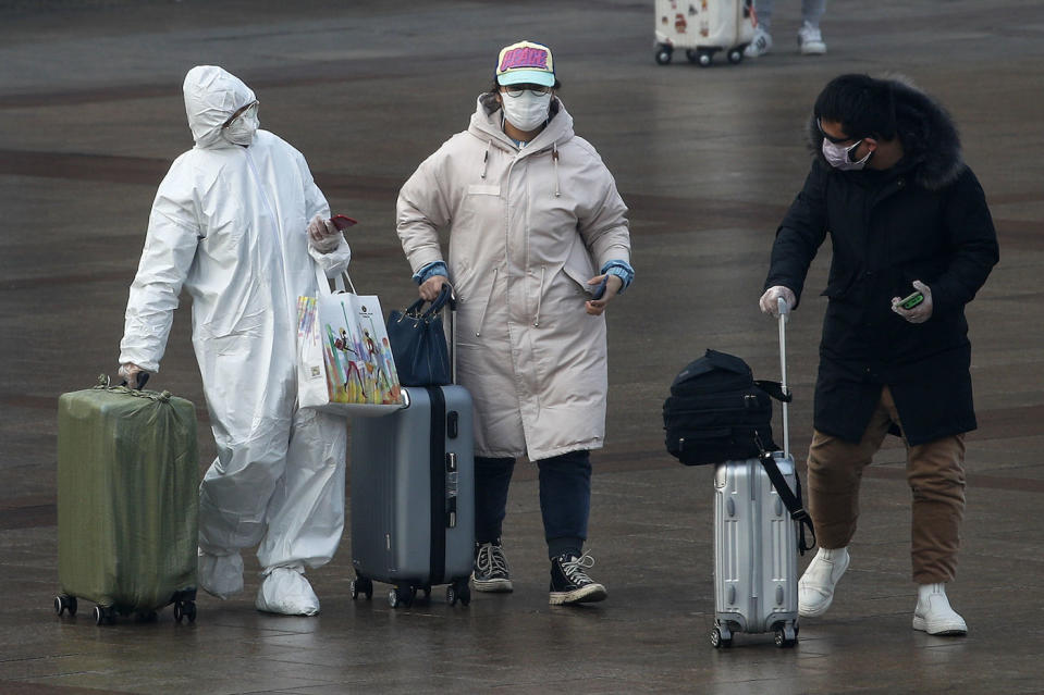 A passenger wearing a full-body protective suit walks out of Beijing railway station in China on Tuesday (AP)