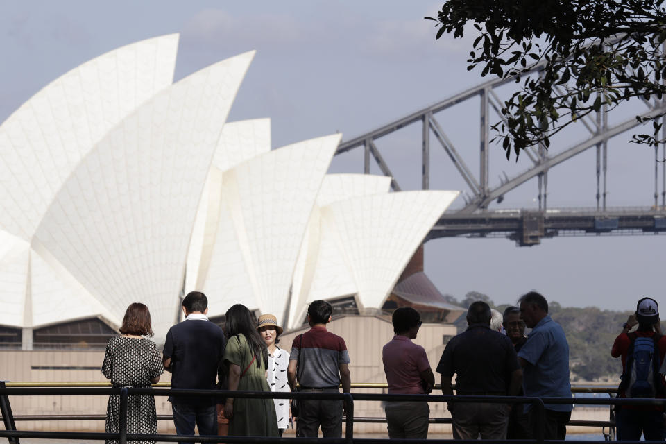 In this Jan. 22, 2020, photo, tourists gather to have their photos taken with the Opera House and Harbour Bridge as a backdrop in Sydney, Australia. Coronavirus has hit the tourism industry hard. Image: AP