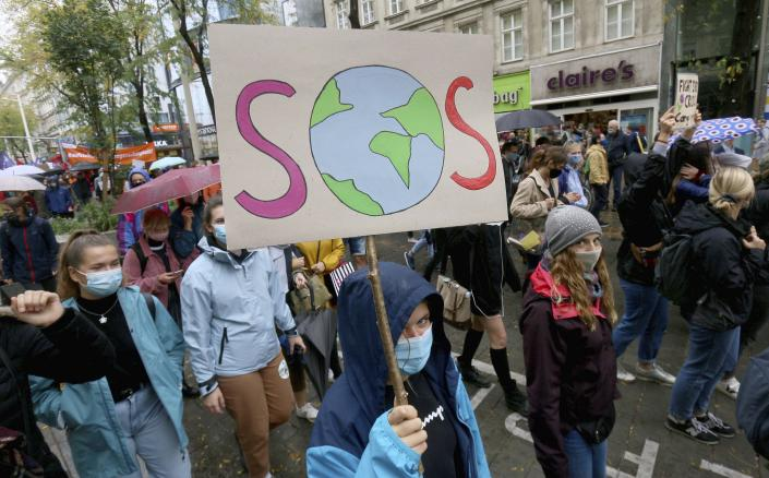 Environmental activists wearing face masks to help protect against the spread of the coronavirus stage during a rally marking the Global Day of Climate Action in Vienna, Austria, Friday, Sept. 25, 2020. (AP Photo/Ronald Zak)
