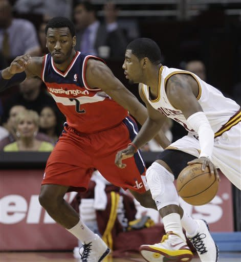 Cleveland Cavaliers' Kyrie Irving, right, drives past Washington Wizards' John Wall in the first quarter in an NBA basketball game on Wednesday, April 25, 2012, in Cleveland. (AP Photo/Tony Dejak)