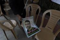 """A Palestinian man gives away posters with a picture of Palestinian prisoner that says """"freedom for the sick prisoner Nasser Abu Ehmad, sentenced for seven life imprisonments and fifty years,"""" during a protest in the West Bank city of Ramallah, Tuesday, Sept. 14, 2021. Hundreds of thousands of Palestinians have passed through a military justice system designed for a temporary occupation that is now well into its sixth decade. Nearly every Palestinian has a loved one who has been locked up in that system at some point, and imprisonment is widely seen as one of the most painful aspects of life under Israeli rule. (AP Photo/Nasser Nasser)"""