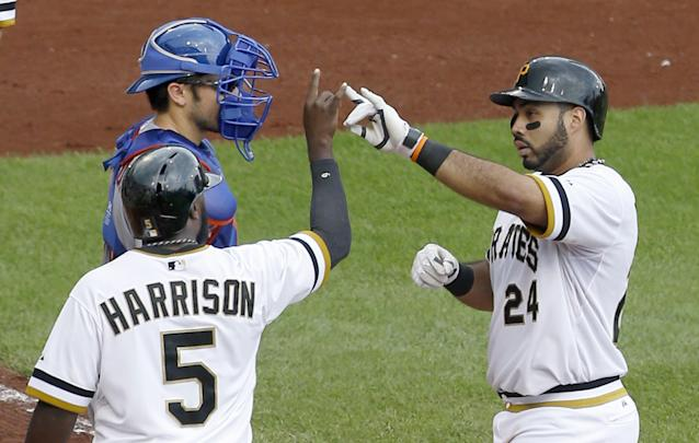 Pittsburgh Pirates' Josh Harrison (5) greets Pedro Alvarez (24) in front of New York Mets catcher Travis d'Arnaud after Alvarez drove him in with a two-run home run in the fourth inning of the baseball game on Sunday, June 29, 2014, in Pittsburgh. (AP Photo/Keith Srakocic)