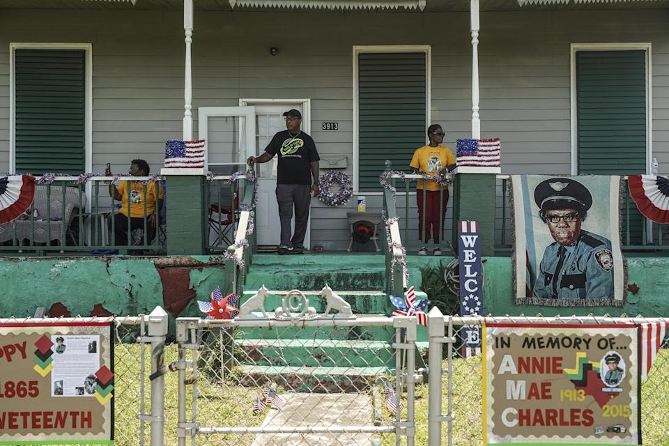 Several people watch from the porch of a house with American flags displayed and commemorative signs.