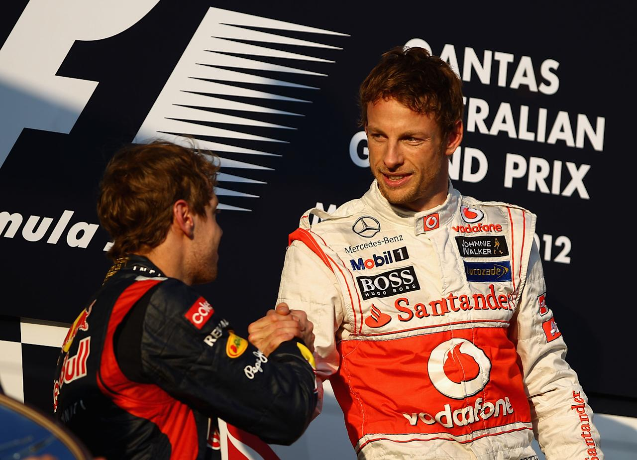 MELBOURNE, AUSTRALIA - MARCH 18:  Race winner Jenson Button (R) of Great Britain and McLaren celebrates with second placed Sebastian Vettel (L) of Germany and Red Bull Racing on the podium following the Australian Formula One Grand Prix at the Albert Park circuit on March 18, 2012 in Melbourne, Australia.  (Photo by Clive Mason/Getty Images)