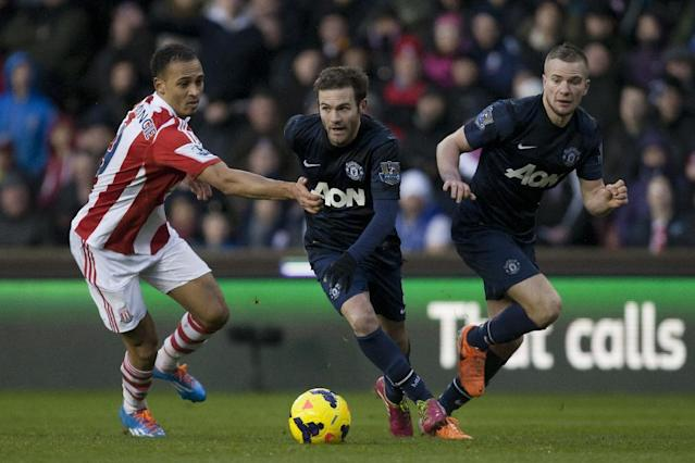 Manchester United's Juan Mata, centre, avoids the attentions of Stoke's Peter Odemwingie, left, as Tom Cleverley looks on during their English Premier League soccer match at the Britannia Stadium, Stoke, England, Saturday Feb. 1, 2014. (AP Photo/Jon Super)