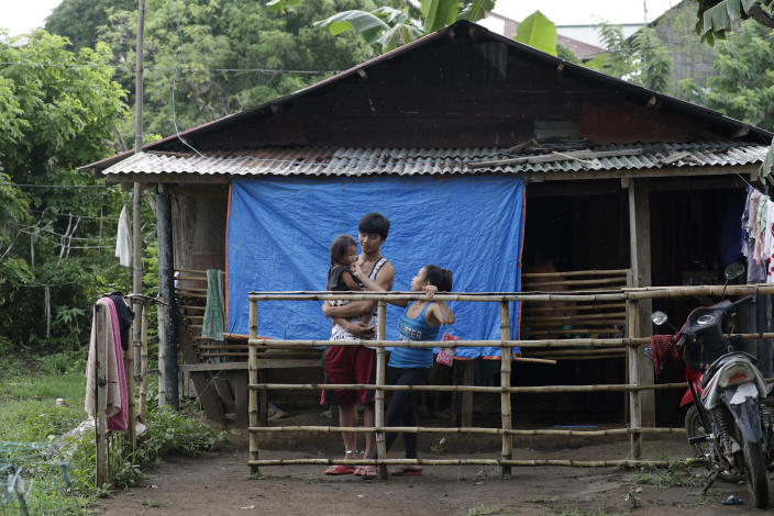 Ronnel Manjares, left, and Trisha May Noche, right, plays with their daughter Crystal outside the house of their relative in Tanauan, Batangas province, Philippines, Wednesday, July 15, 2020. Their 16-day-old son Kobe was heralded as the country's youngest COVID-19 survivor. But the relief and joy proved didn't last. Three days later, Kobe died on June 4 from complications of Hirschsprung disease, a rare birth defect. (AP Photo/Aaron Favila) (AP Photo/Aaron Favila)