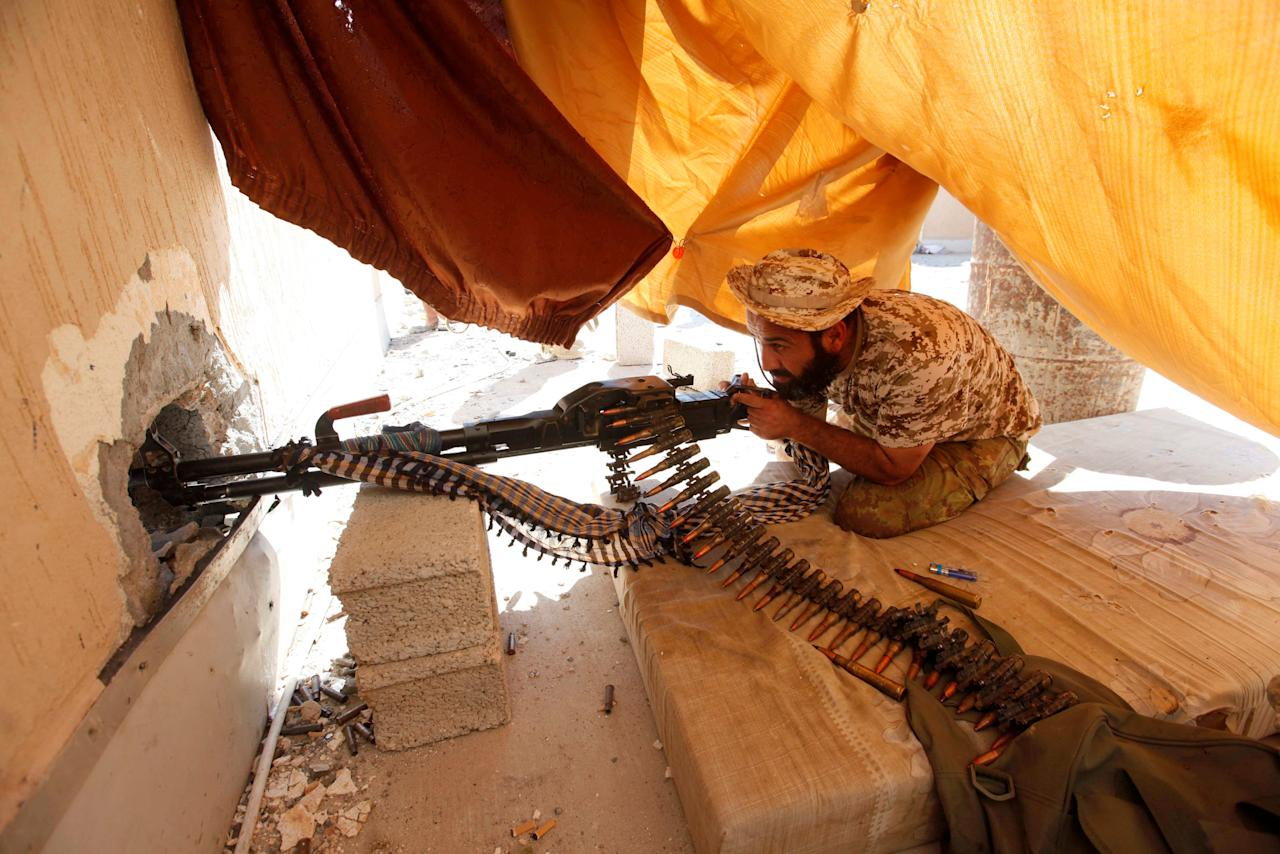 A fighter from Libyan forces allied with the U.N.-backed government aims his weapon as he takes a position on a building rooftop during a battle with Islamic State militants in Sirte, Libya September 24, 2016. REUTERS/Ismail Zitouny     TPX IMAGES OF THE DAY