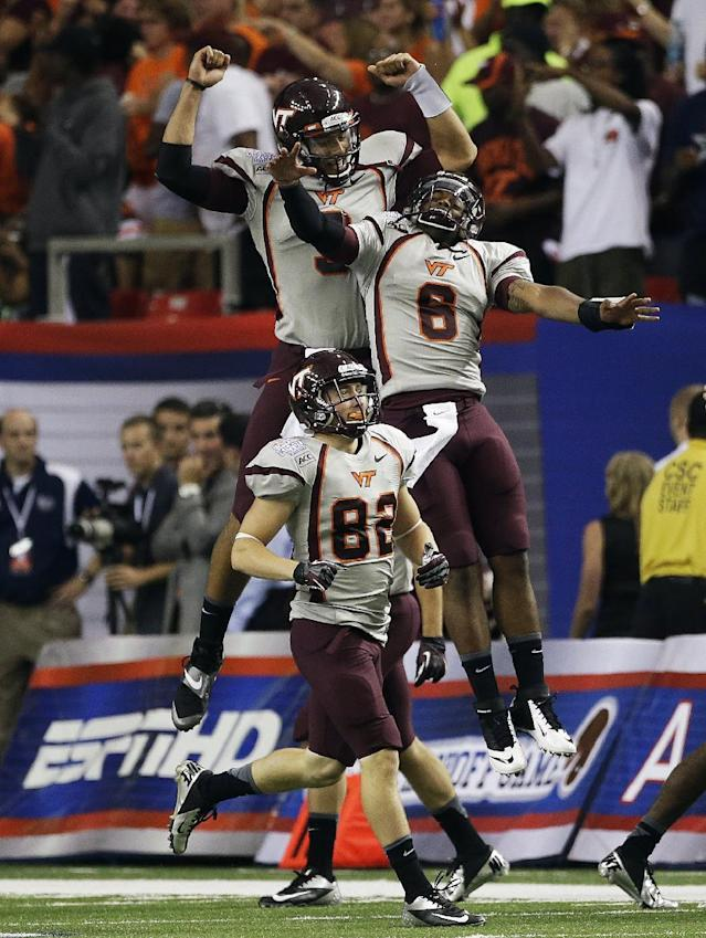 Virginia Tech quarterback Logan Thomas (3) celebrates with safety Detrick Bonner (8) and wide receiver Willie Byrn (82) after the Hokies scored in the first half of an NCAA college football game against Alabama, Saturday, Aug. 31, 2013, in Atlanta. (AP Photo/Dave Martin)