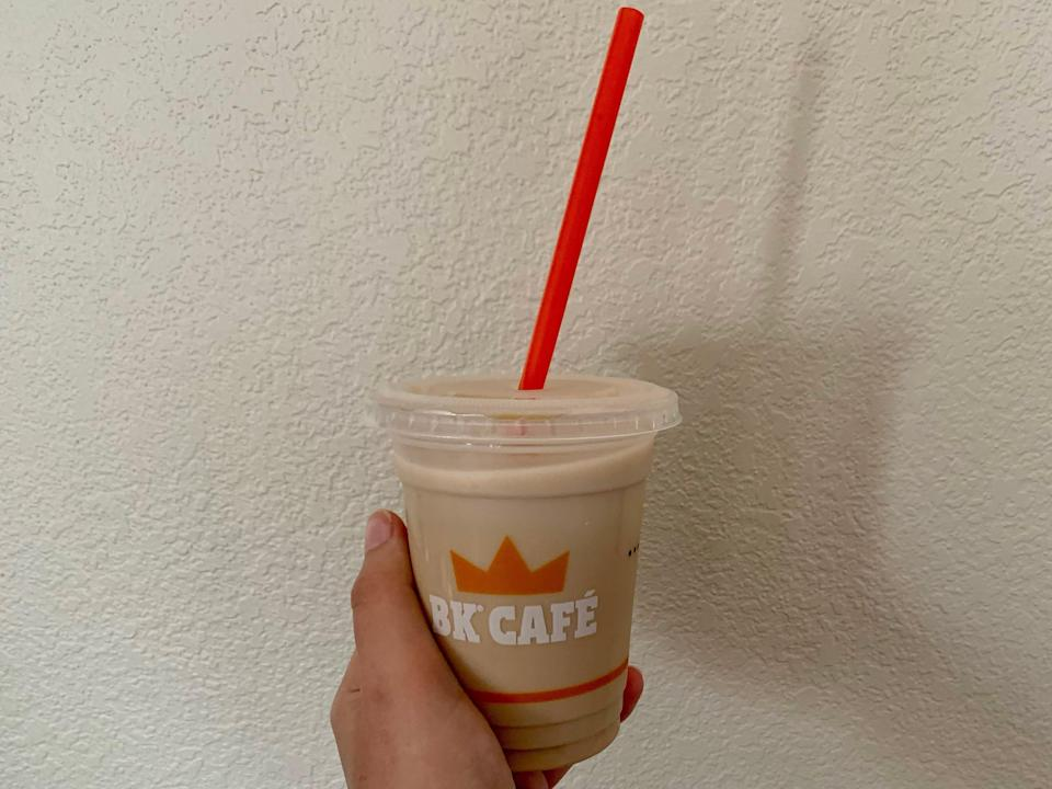 a hand holding a burger king iced coffee in front of a beige wall