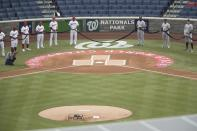 The New York Yankees and the Washington Nationals hold a black ribbon to honor Black Lives Matter before playing an opening day baseball game at Nationals Park, Thursday, July 23, 2020, in Washington. (AP Photo/Andrew Harnik)