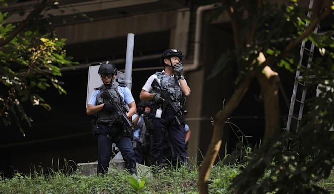 Armed police officers search the area where a suspected explosive device was found near Tai Wai MTR station on February 20. Photo: Sam Tsang